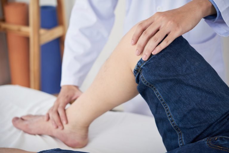 Anonymous medical practitioner touching knee and ankle of crop man during rehabilitation session in doctor's office