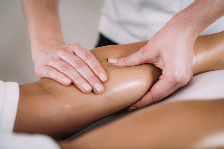 Physiotherapist massaging female patient with injured calf. Sports injury treatment.