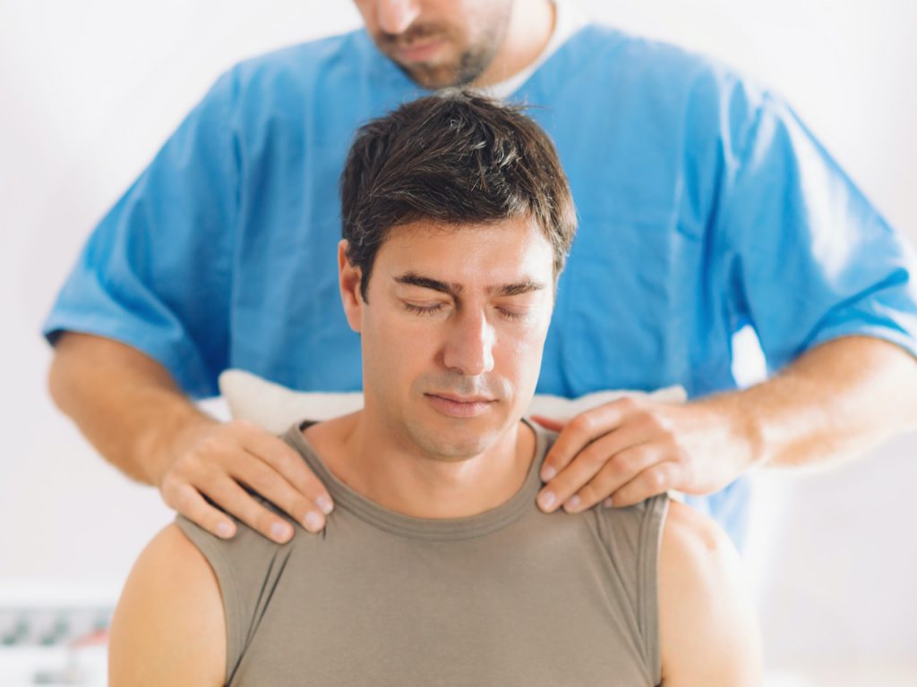 Physiotherapist doing healing treatment on man's shoulders and neck, Therapist wearing blue uniform, Osteopath,  Chiropractic adjustment, pain relief concept