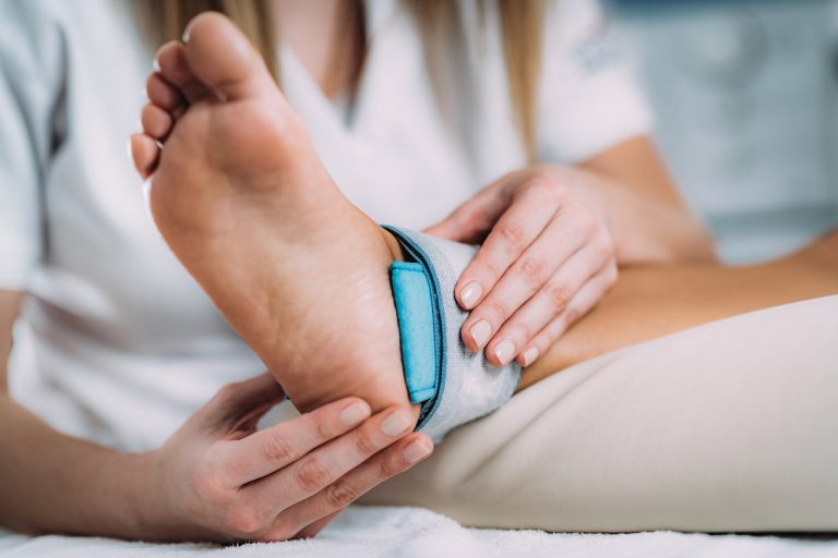TENS, Transcutaneous Electrical Nerve Stimulation in Physical Therapy. Therapist Positioning Electrodes onto Patient's Ankle Joint